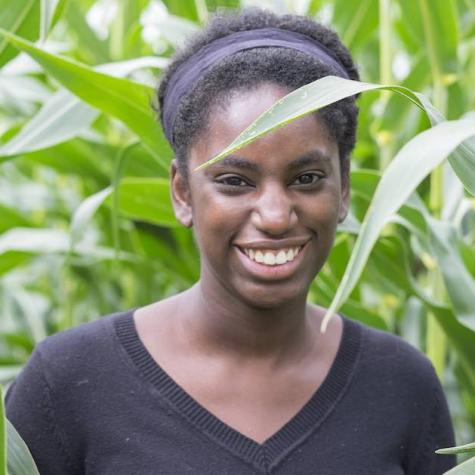 woman in a corn field with a black shirt and big smile