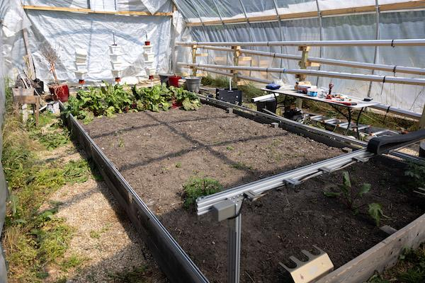 High tunnel garden with plants and equipment in the foreground