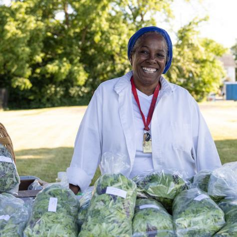 Woman in a white lab coat with bags of fresh lettuce in front of her