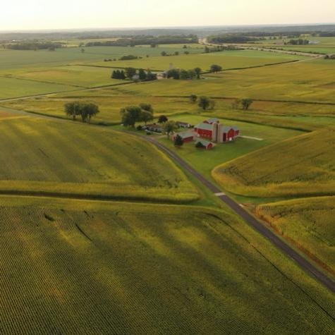 drone view of farm fields, a road, farm house, sparse trees and a hazy sky