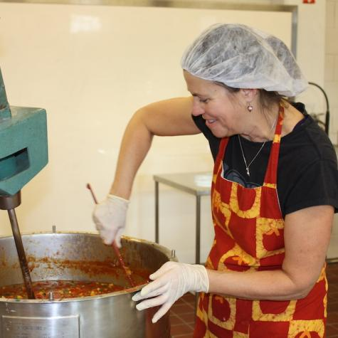 woman in a hairnet, stirring a large pot of soup with gloves and a red and yellow apron
